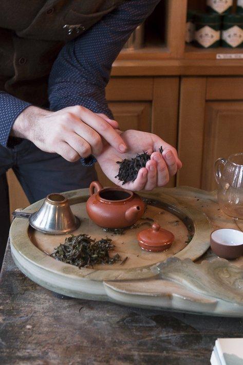 mains mettant une pincée de thé